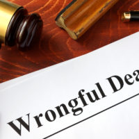wrongful death document, gavel, spectacles and pen on table