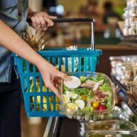 a woman buying a salad at a deli