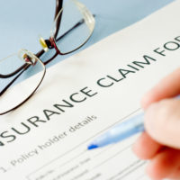 person filling out insurance claim form with glasses on table