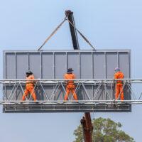 construction workers on billboard catwalk
