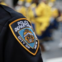 NYPD officer's shoulder showing logo with blurred background