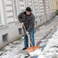 man shoveling snow out of his property