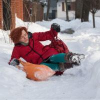 woman slips and falls on snowy sidewalk