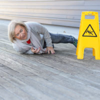 Senior woman slipping and falling on a wet surface