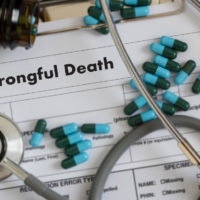 Wrongful Death form with stethoscope and pills on top
