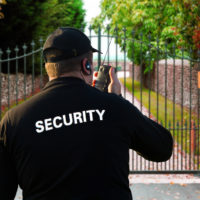 security guard on walkie talkie in front of property