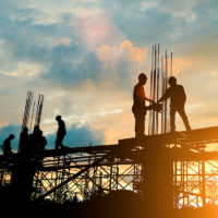 Silhouette of construction team working on roof