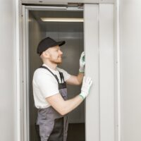 Lift machinist man repairing elevator fixing or adjusting mechanism