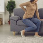 Young woman wants to get up from the sofa but feels a sudden pain in her lower back